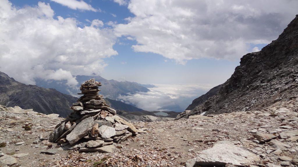 Depuis le col, versant italien : derrière le cairn la fin du vallon de Savine et à droite le lac d'Agnello