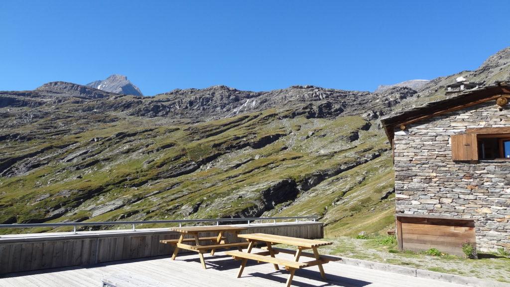Depuis la terrasse panoramique du refuge, vue sur les barres rocheuses situées sous le lac et le glacier de l'Arpont.